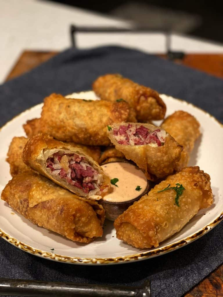 a plate of reuben egg rolls with Russian dressing in a wooden bowl