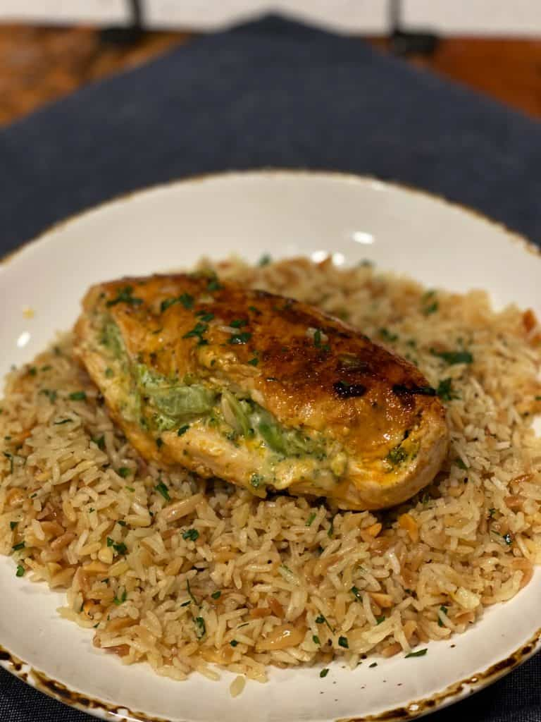 One cheesy broccoli stuffed chicken breast sitting on a top a bowl of almond rice pilaf
