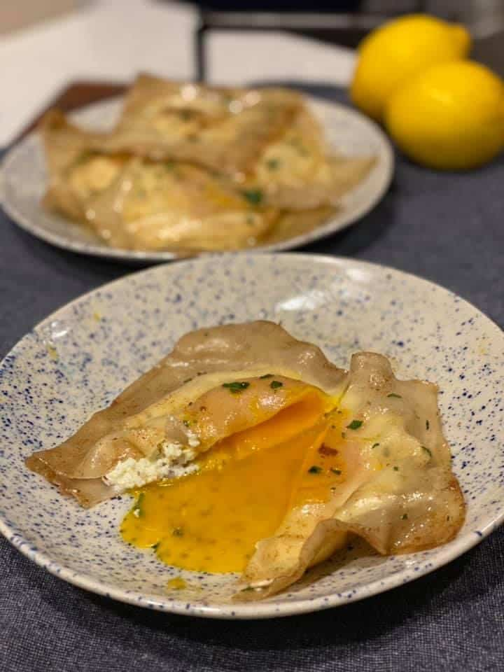 a close up of an egg yolk ricotta ravioli cut open with the yolk running onto the plate