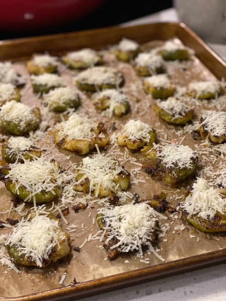 a pan of smashed Brussels sprouts topped with shredded Parmesan cheese