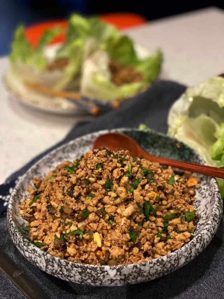 a bowl of ground chicken for chicken lettuce wraps with lettuce leaves in the background