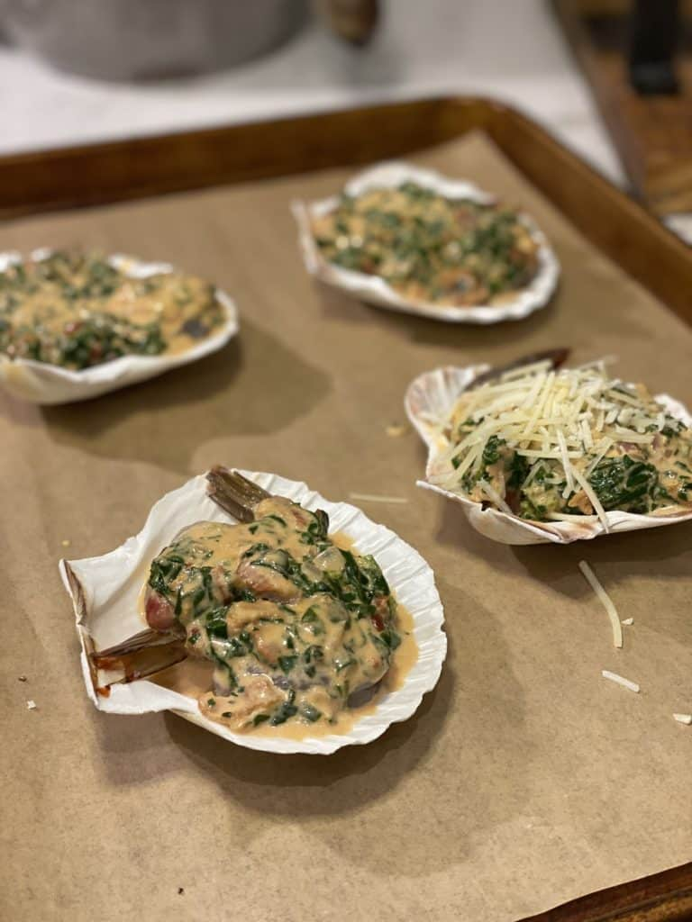four baking shells on a parchment lined baking pan filled with two shrimp each and Rockefeller sauce