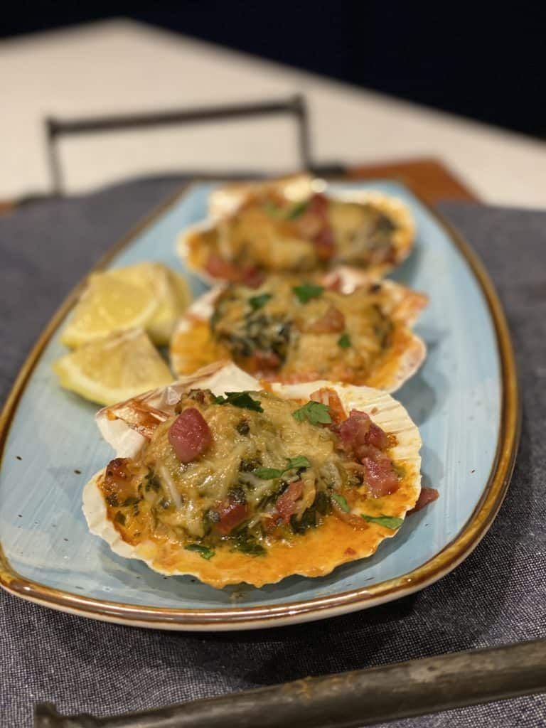 three baking shells on a blue plate filled with shrimp rockefeller