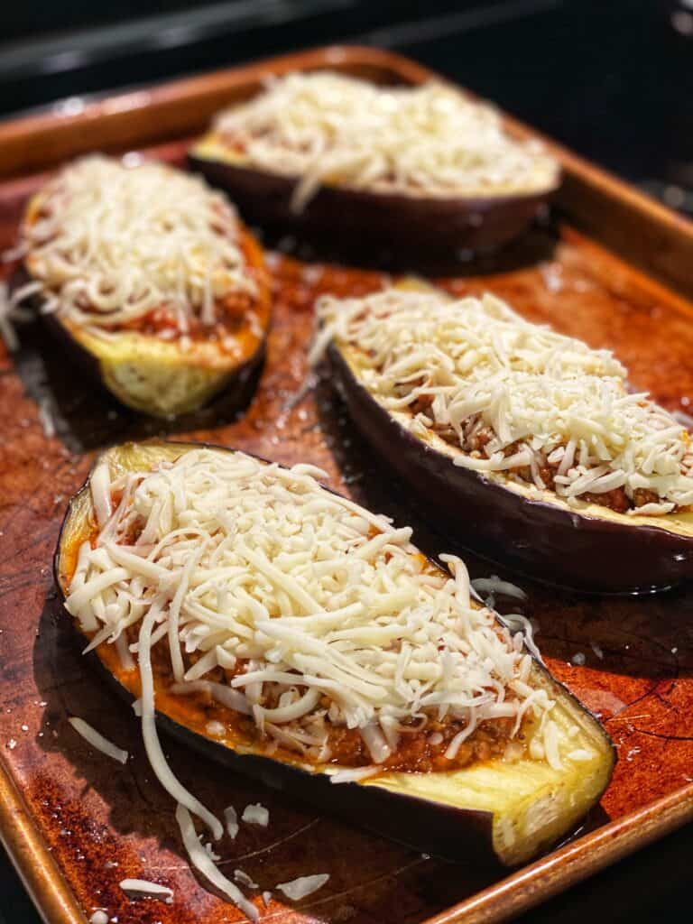 roasted eggplant boats filled with meat sauce and topped with cheese on a sheet pan ready to be baked