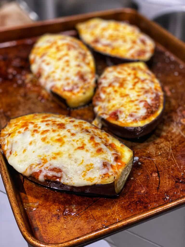 four roasted eggplant boats on top of a baking sheet