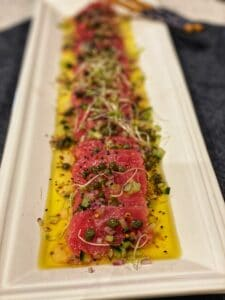 a white long platter filled with tuna crudo