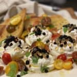 a plate of deconstructed burrata salad garnished with golden and fig balsamic caviar