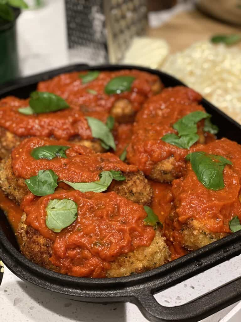 a pan of rolled chicken parmesan covered with sauce ready to bake in the challenger pan