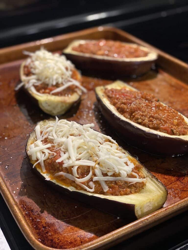 eggplant boats filled with meat sauce and topped with cheese on a sheet pan ready to be baked