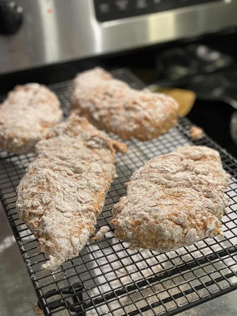 four floured coated chicken pieces sitting on a baking rack