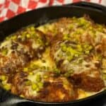 Nashville hot chicken bake in a cast iron pan covered in a sour cream sauce and garnished with diced pickles