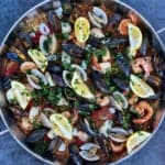 a pan of easy seafood paella filled with mussels, clams, lemon wedges and shrimp sitting on blue concrete