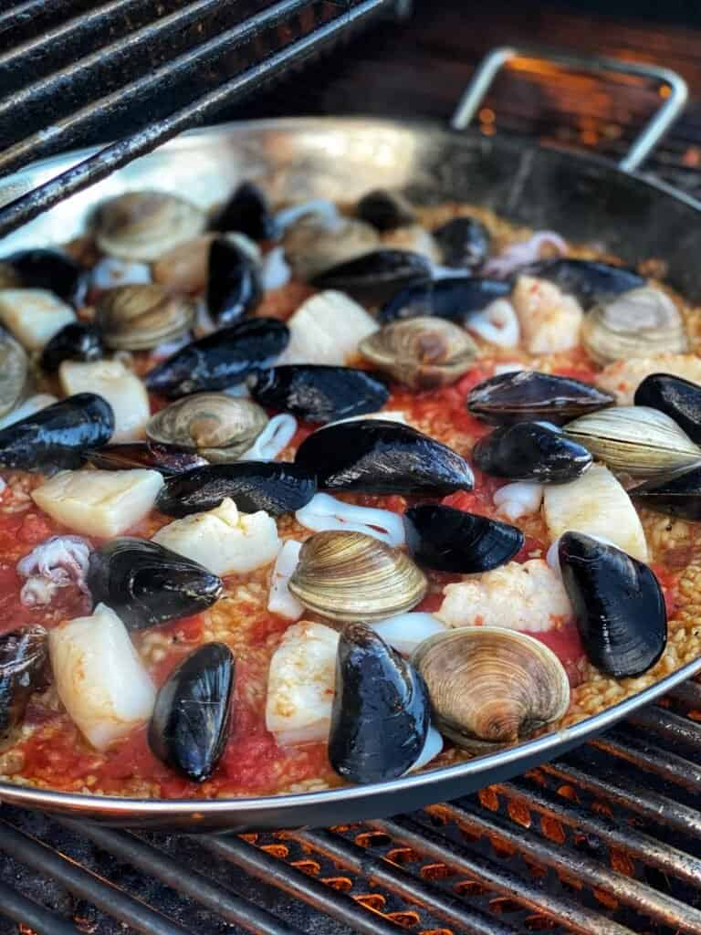 seafood cooking in a paella pan with rice on a grill