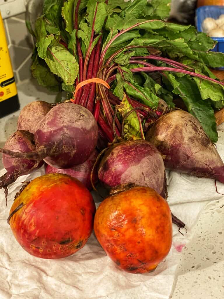 a bundle of red beets with two golden beets in the foreground