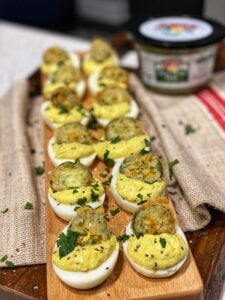 a wooden tray of 12 salsa verde deviled eggs