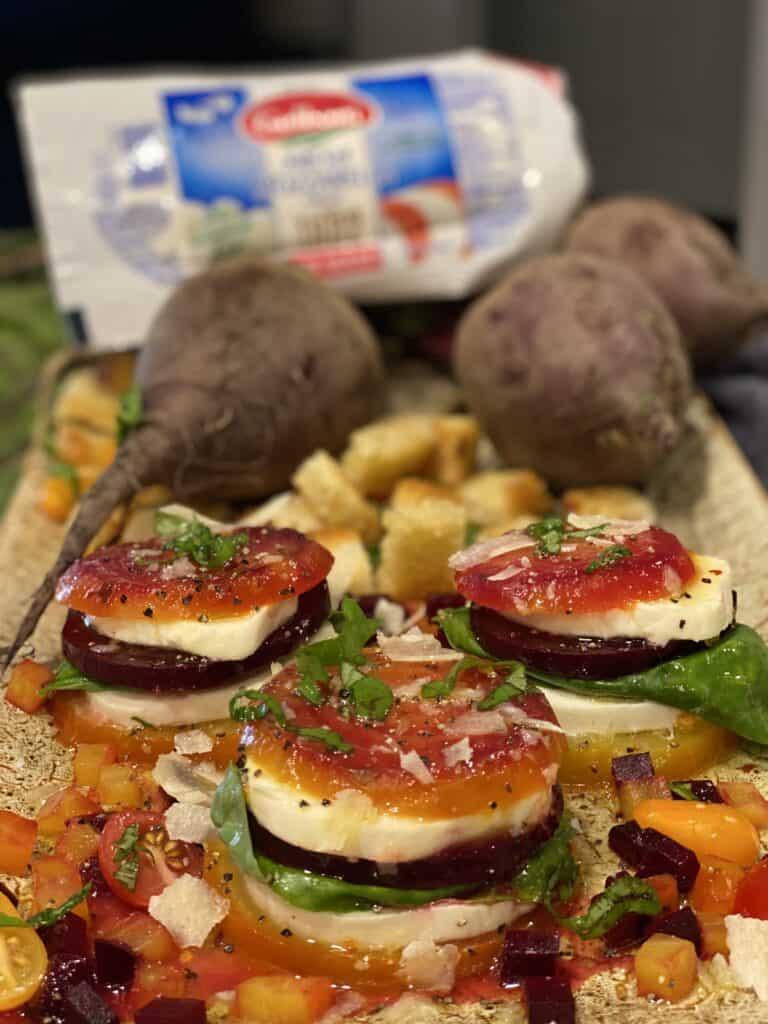 a platter of roasted beet caprese towers garnished with fresh basil with a log of Galbani fresh mozzarella in the background