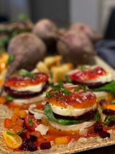 a platter of roasted beet caprese towers garnished with fresh basil