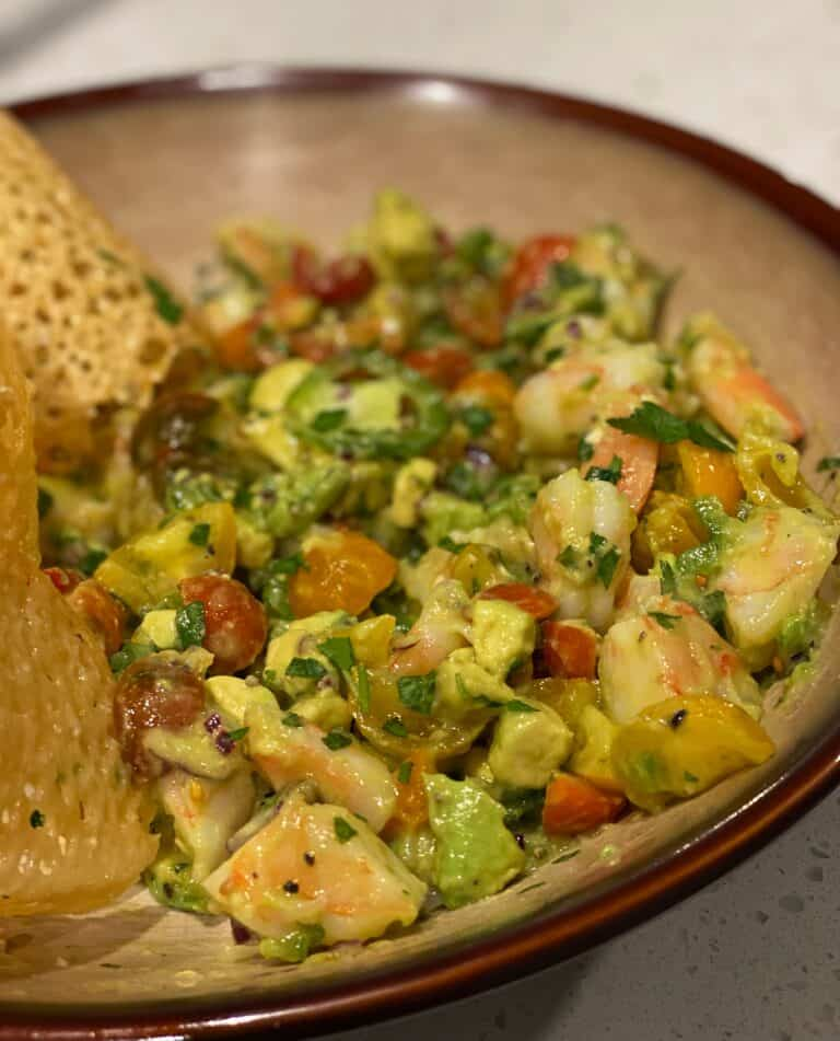a light brown bowl filled with the best avocado shrimp salad with a side of Parmesan crisps