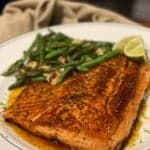 a filet of lime honey butter salmon sitting on a round platter with green beans and lime wedges