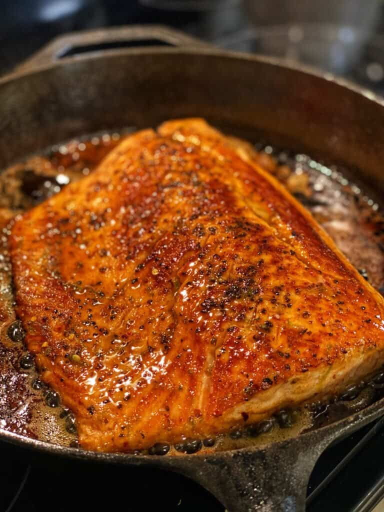 a filet of salmon searing in a cast iron pan