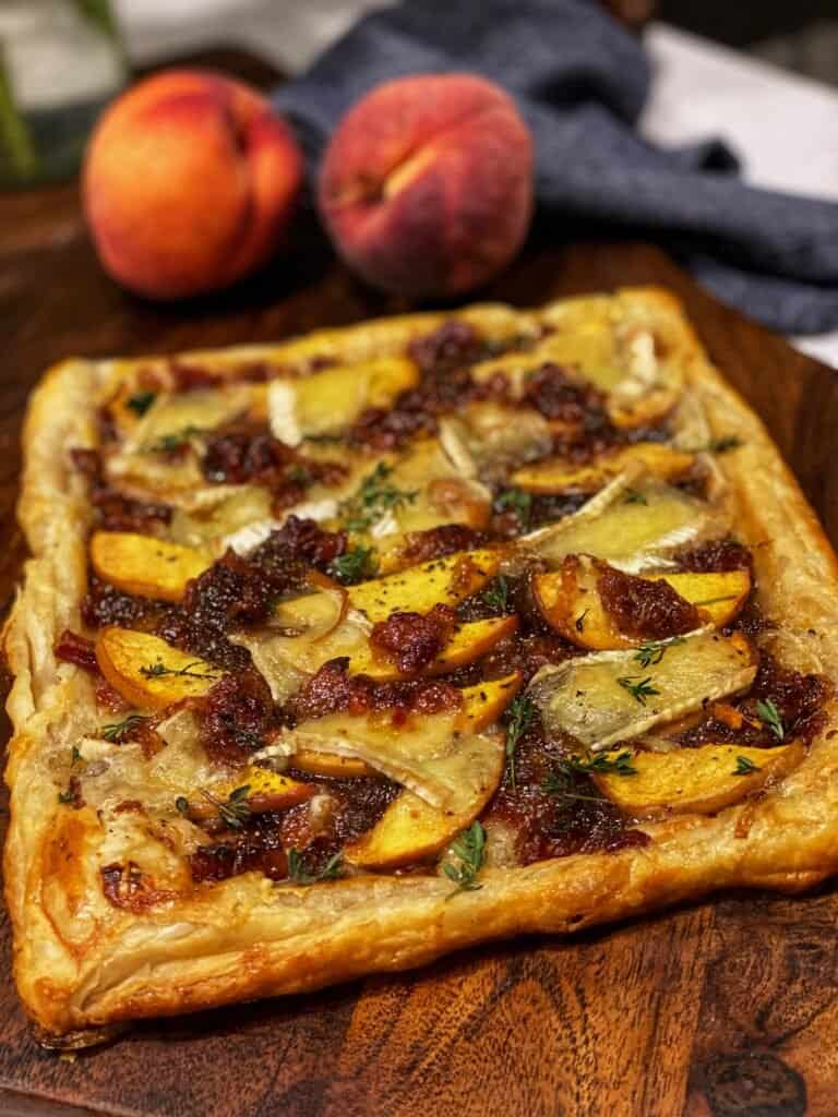 a puff pastry tart filled with brie cheese, peaches and shallot bacon jam