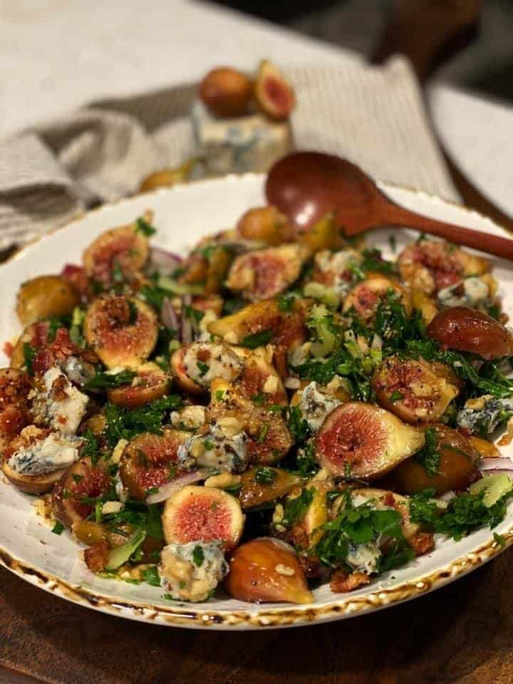 a white bowl filled with fresh fig parsley salad