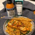 a bowl of spicy sesame noodles topped with a piece of kimchi mayo seared sea bass with a bottle of kimchi mayo and a bottle of gochujang in the background