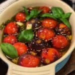 a blue oven safe dish filled with fresh tomatoes, basil, garlic and olive oil for confit tomatoes and garlic