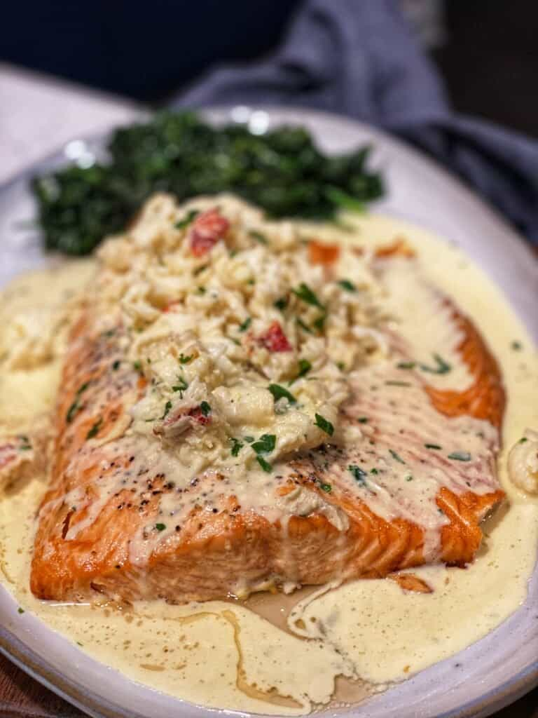 a platter with roasted salmon topped with lobster newburg sauce
