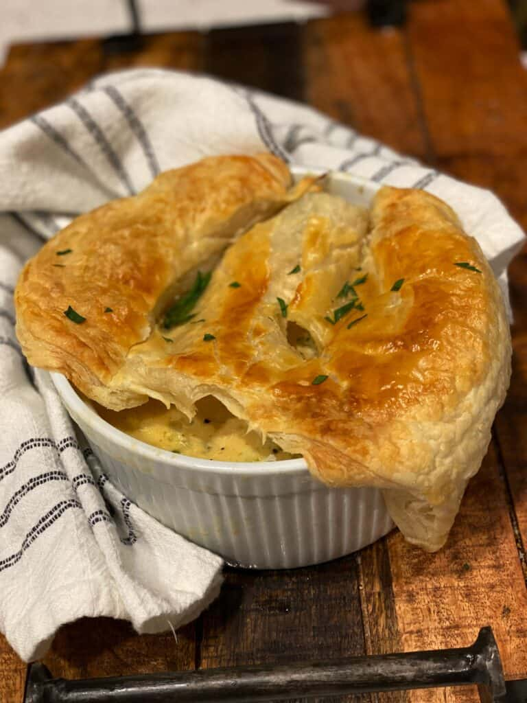 a medium-sized white ramekin filled with broccoli chicken pot pie topped with a flaky puff pastry and garnished with fresh chopped parsley